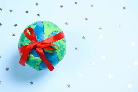 Planet Earth with red ribbon among the stars on a blue background. Ecology, environmental protection. World Earth Day concept.