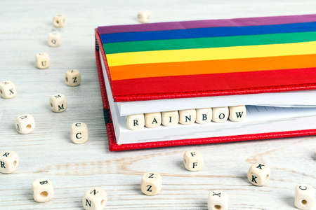 Word Rainbow written in wooden blocks in red notebook with rainbow flag on wooden table. Pride Month in June.