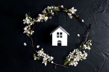 Miniature toy house with cherry blossom branches on the black background.
