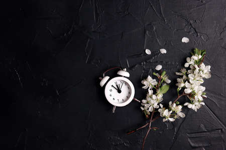 Small white alarm clock with apple blossom branches on a black background. Springtime border with copy space.