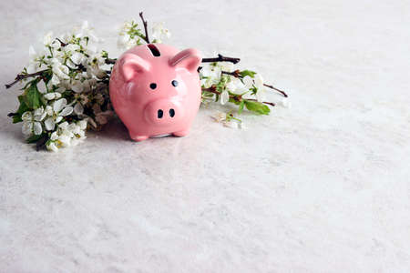 Pink piggy bank with apple blossom branches on a light marble table with copy space for text.