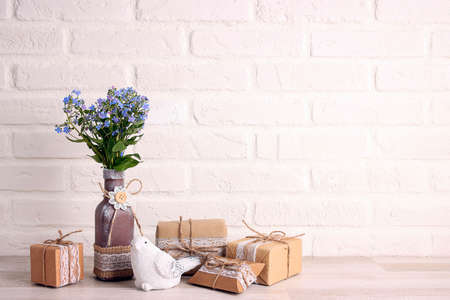 Forget-me-not flowers in a vase with gifts and bird on a white brick wall background. Copy space. Spring holidays, Mothers Day, Easter concept.