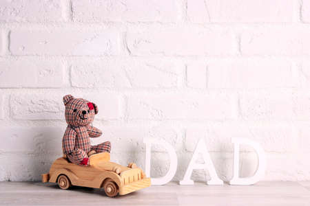 Father's day message with toy bear and wooden car on a white brick wall background. Copy space for text.