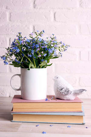 White coffee mug with bouquet of forget-me-not flowers, books and bird on the white brick wall background. Space for text or design.