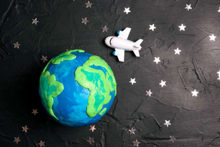 Plane is flying through the world over the Earth globe among the stars on a black background. Tourism, travel concept.
