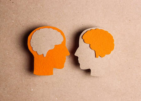 Cardboard profiles with brain symbol on a brown background .. World Multiple Sclerosis Day. Communication, dialogue, exchange of views concept.