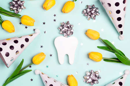 Festive dental background with tooth, holiday caps and yellow tulips on a blue background. Happy Dentist's Day concept.