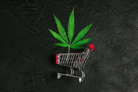 Cannabis leaf in shopping cart on black background. Medical weed. Fast marijuana delivery.