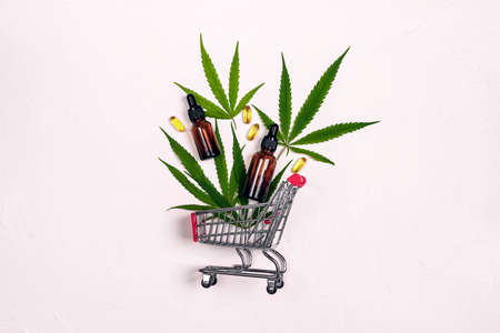 Mini supermarket trolley with Cannabis extract oil in a bottles, capsules and marijuana leaves on a white background. Cannabis shop sale. Alternative medicine.