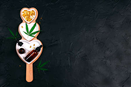 Heart dish with glass bottles with cbd oil, capsules and hemp leaves on black background. Top view, flat lay, copy space. Alternative medicine.