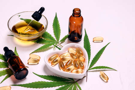 Capsules, bottles and bowl with cbd oil and hemp leaves on white background. Alternative medicine. Essential natural oils for cosmetics. Фото со стока