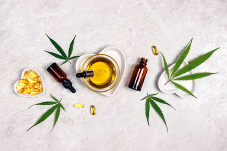 Flat lay composition with hemp leaves, capsules, bottles and bowl with CBD oil and THC tincture on light marble table. Essential natural oils for cosmetics. Фото со стока