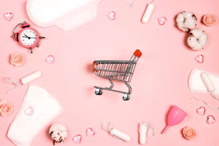 Shopping cart with menstruation period accessories on pink background. Sanitary pads, tampons, menstrual cup and cotton bolls. Flat lay, top view.