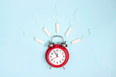 Ringing red alarm clock with sanitary female tampons on blue background. Menstruation cycle period, woman hygiene.