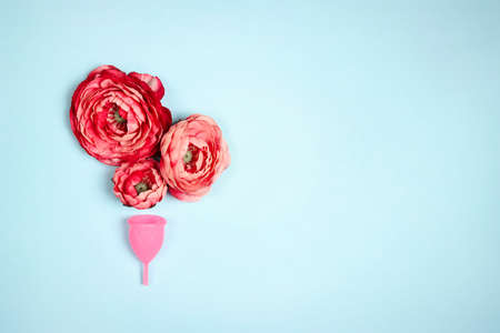 Menstrual cup peony flowers on a blue background. Women's health, hygiene concept. Copy space for text.