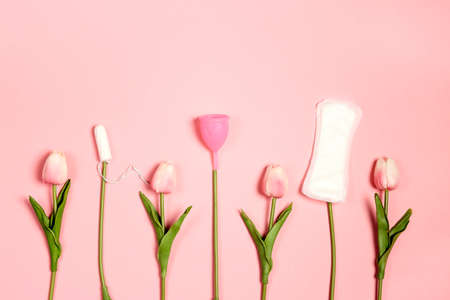 Different types of feminine hygiene products. Tampons, menstrual cup and sanitary pads like tulip flowers on pink background.