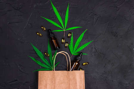 Brown paper shopping bag with green marijuana leaves, Cannabis extract oil in a bottles and capsules on black background. Medical cannabis shopping and store.