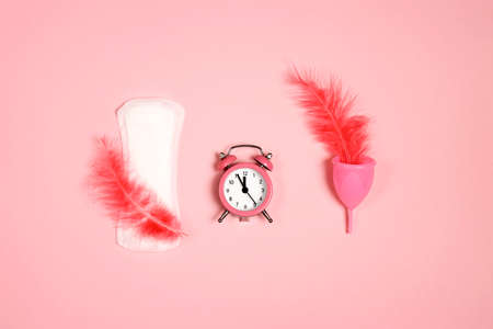 Menstrual pad and cup with feathers and alarm clock on pink background. Menstruation cycle period, woman hygiene.