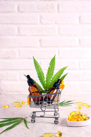 Mini supermarket trolley with Cannabis extract oil in a bottles, capsules and marijuana leaves on a white brick wall background. Vertical image with copy space. Cannabis shop sale. Alternative medicine.