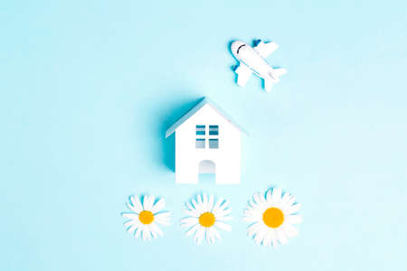 Small toy house and airplane with chamomiles on a blue background. Summer travel and vacation concept.
