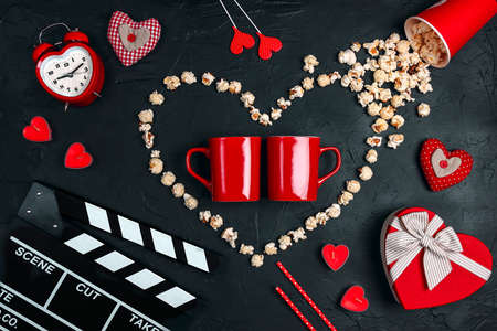 Two red mugs, movie clapper board, popcorn heart, gift box, candles and other love objects on black background. Valentine's Day, date and romantic evening concept. Love story movies.
