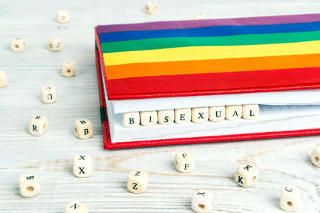 Word Bisexual written in wooden blocks in red notebook with rainbow LGBT flag on wooden table. LGBT Pride Month in June.