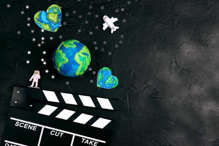 Movie clapper board with globe, astronaut and stars on black background. Space cinema film concept with copy space for text. Фото со стока