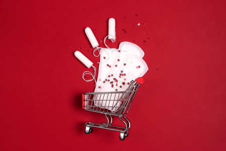 Shopping cart with menstruation period accessories on red background. Sanitary pads, tampons and star sequins. Flat lay, top view with copy space.