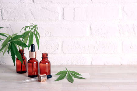 Bottles with CBD oil, droppers and marijuana leaves on a white brick wall with copy space. Medical hemp.