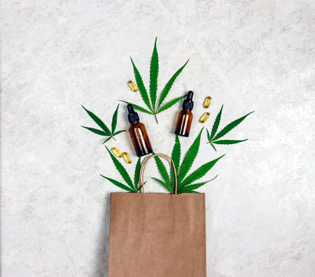 Brown paper shopping bag with green marijuana leaves, Cannabis extract oil in a bottles and capsules on light marble background. Medical cannabis shopping and store.