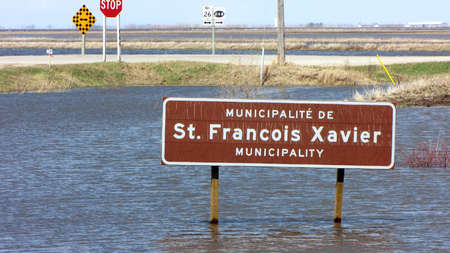 assiniboine: St. Francois Xavier, Canada - May 8, 2011: The municipal road sign stands submerged in floodwater from the nearby Assiniboine River.  The province of Manitoba issued a State of Emergency, which includes this area.  Soldiers are assisting in raising dikes.