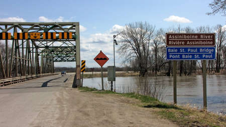 assiniboine: Southern Manitoba - May 8, 2011: The Assiniboine River has spilled its banks and is level with this bridge in the municipality of St. Francois Xavier.  The province of Manitoba has declared a State of Emergency which includes this area.