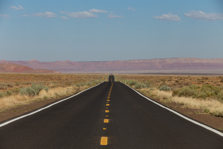 a view of endless straight road running through the barren scenery of the American Southwest with sky and clouds