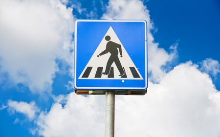 Old traffic sign pedestrian crossing with blue sky photo