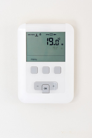 control panel: Digital thermostat on white wall