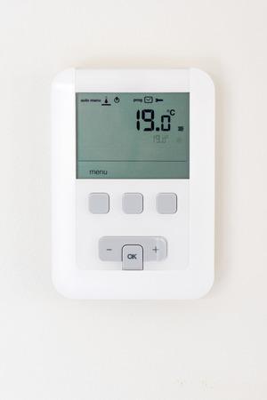 tablero de control: termostato digital en la pared blanca Foto de archivo