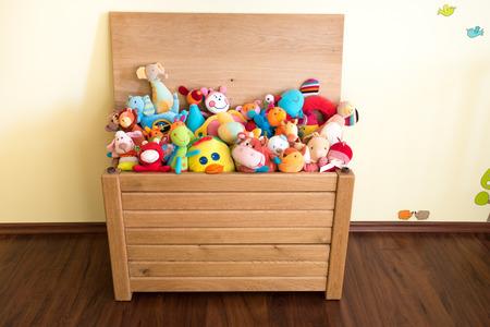 juguetes de madera: Toy Box llena de juguetes blandos en la habitaci�n de un ni�o Foto de archivo