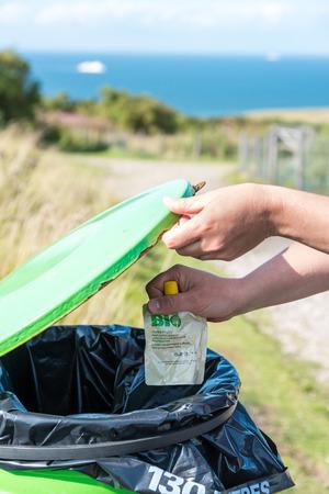 botes de basura: Mano de la mujer lanzando botes de basura en el embalaje. Foto de archivo