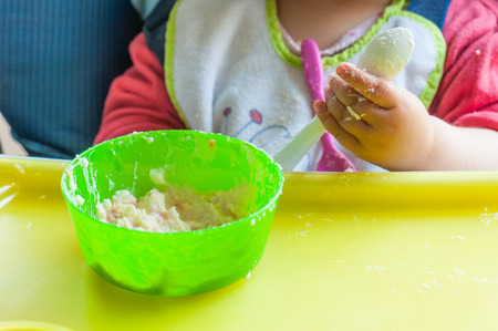 mash: Little girls eating mash and playing with his plate