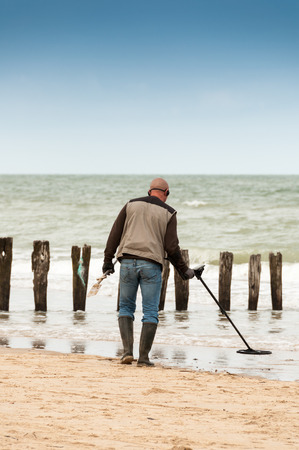 man searching: man searching for a precious metal using a metal detector Stock Photo
