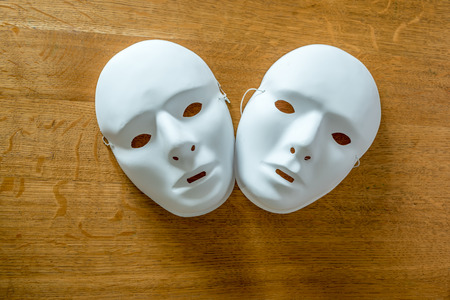 play acting: Two masks on a wooden background
