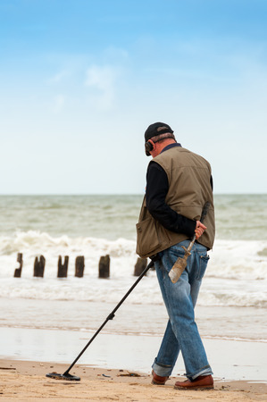 searching for: man searching for a precious metal using a metal detector Stock Photo