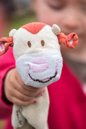 cuddly toy: little girl holding a cow, cuddly toy Stock Photo
