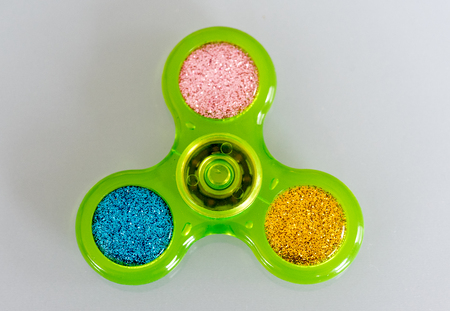 Green fidget spinner stress relieving toy on white background