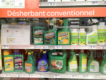 PARIS, FRANCE - NOVEMBER 11, 2017: Shelves with a variety of Herbicides in a french Hypermarket. Roundup is a brand-name of an herbicide containing glyphosate, made by Monsanto Company.
