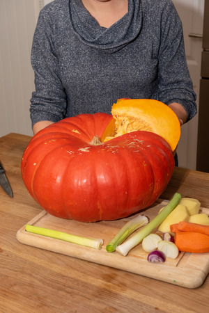 woman cutting a pumpkin to make a soup Imagens