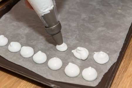 Woman making homemade meringues in a private kitchen Imagens