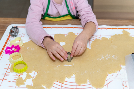 Child cooking traditional cakes for christmas