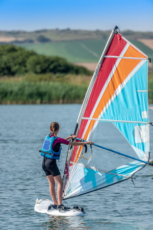 Young girl learning to windsurf on a lake