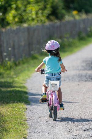 Little girl riding a bike on a path Фото со стока